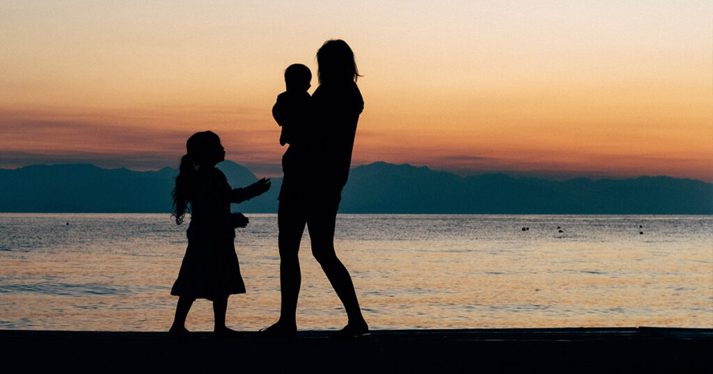 silhouette of an adult and two kids on the beach with the sun setting behind them